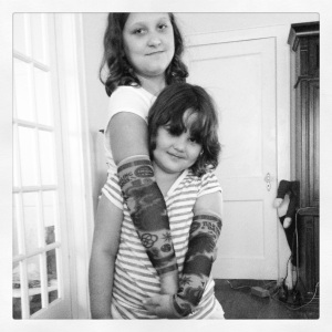 playing with their tattoo sleeves they got from the circus.